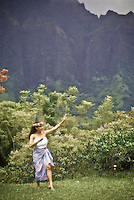 Hawaiian woman dancing the hula near the Koolau mountains