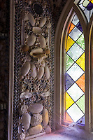 A detail of one of the shell-encrusted window surrounds with sunlight pouring through the stained glass window