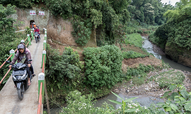 29 JAN, 2018, Bandung, Indonesia: Motobikes cross a bridge over a rubbish filled section of the Cihaur tributary at Pangkalan village down from Saguling dam. The tributary feeds the Citarum river, listed as one of the most polluted rivers in the world.  It will soon be the main water supply system for Jakarta as the bores that have been dug into the aquifers dry but it also supports agriculture, fishery, industry, sewerage and electricity.  The Indonesian Government is moving to urgently try to clean the system up but it is fighting massive infrastructure issues and toxic industrial dumping.    Picture by Graham Crouch/The Australian