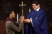 Priest distributes communion wine to parishiner during mass. Communion.