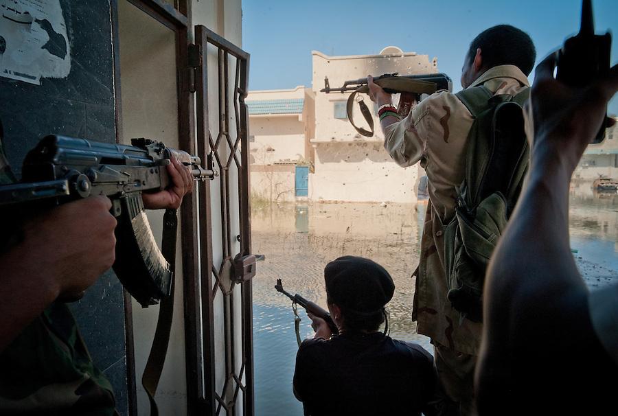 Anti-Gaddafi fighters exchange fire with pro-Gaddafi snipers in Sirte, Libya.