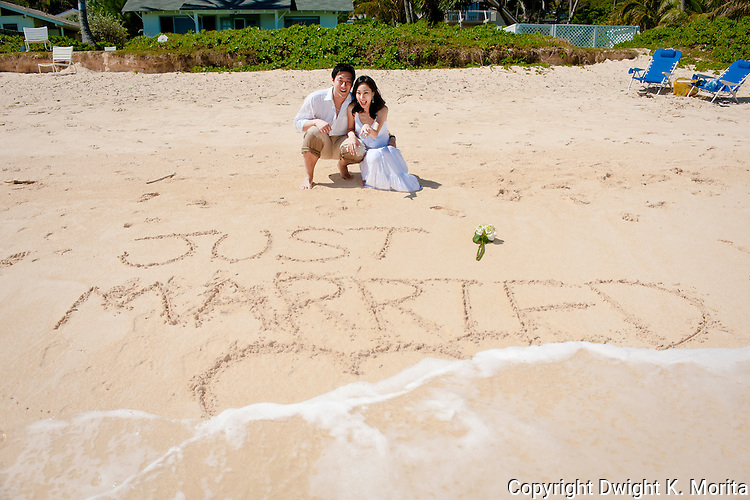 """Asian bride and groom watch a wave wash over their """"Just Married"""" writing in the sand during a stroll on Lanikai beach. The couple celebrate their wedding with a honeymoon in Hawaii."""