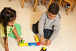 Education Preschool 3-4 year olds boy and girl playing with Duplo color plastic building bricks