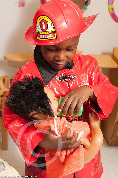 Education preschool pretend play boy in firefighter costume holding doll and giving it a drink with cup