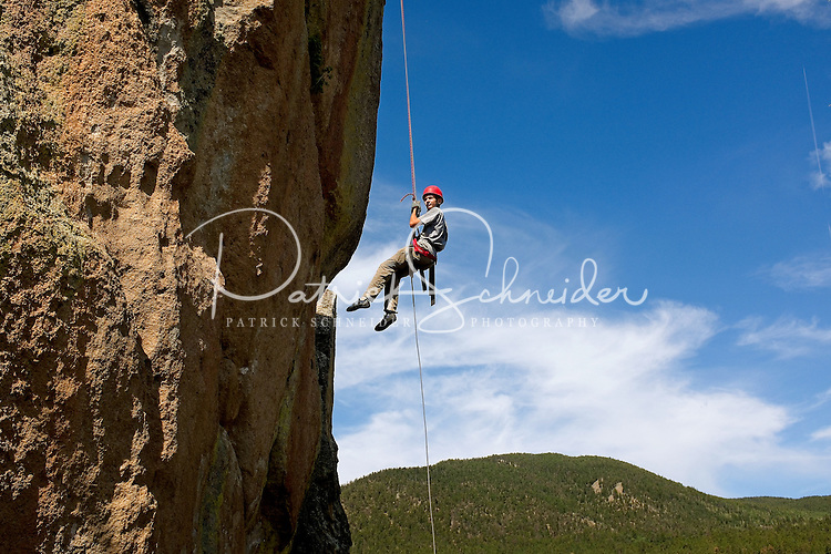 Photo story of Philmont Scout Ranch in Cimarron, New Mexico, taken during a Boy Scout Troop backpack trip in the summer of 2013. Photo is part of a comprehensive picture package which shows in-depth photography of a BSA Ventures crew on a trek. In this photo, a BSA Venture Crew  member rappels off of the front face of a natural rock, 60- feet off of the ground. The climbing was taking place at the  Cimarroncito Camp in the backcountry at Philmont Scout Ranch.   <br /> <br /> The  Photo by travel photograph: PatrickschneiderPhoto.com