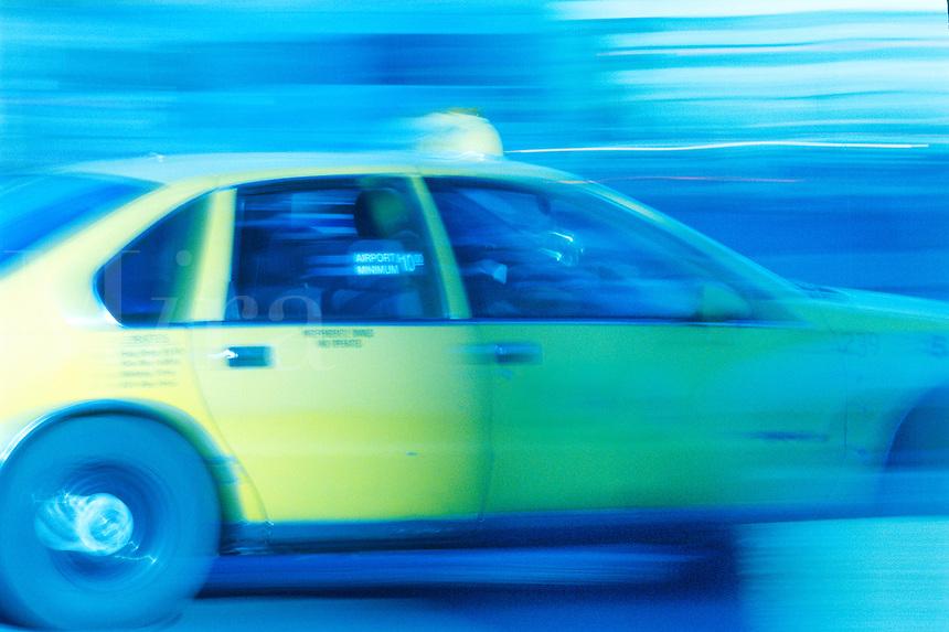 Blurred taxi speeding through busy city