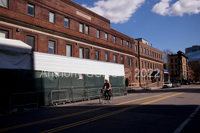 """Brooklyn, New York<br /> April 4, 2020<br /> <br /> Huge refrigerated trailers by the Brooklyn Hospital Center in Fort Greene for the corona virus dead.<br /> <br /> The coronavirus has transformed urban architectural spaces with proximity fear. Not entirely void of humanity, social distancing, within expansive city environments has created a landscape of aggrandizing physical structures and expanding spaces while diminishing the scale of humans. Face masks enhance the anonymity of """"the person"""", reducing them to a figure or an uninterrupted shadow falling on a surface."""