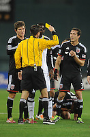 Washington D.C. - March 8, 2014: Referee Andres Pfefferkorn gives a yellow card to Tony Tchani (6) of the Columbus Crew after a hard tackle on Luis Silva (11) of D.C. United.  The Columbus Crew defeated D.C. United 3-0 during the opening game of the 2014 season at RFK Stadium.