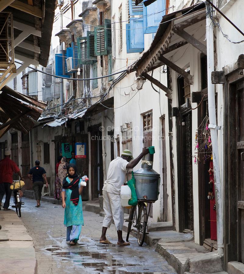 Stone Town Street Scene, Zanzibar, Tanzania.  Milk Man Making Delivery, Young Girl Walking.