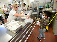 Cindy Wells (left), cafeteria manager at Sutton Elementary School, hands sacked lunches Thursday, June 3, 2021, to Sebastian Uribe, 5, a rising first-grader at the school, while handing out meals to students at the school in Fort Smith. Visit nwaonline.com/210606Daily/ for today's photo gallery.<br /> (NWA Democrat-Gazette/Andy Shupe)