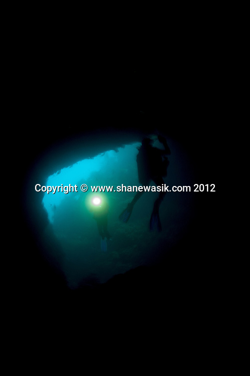 Inside the cavern is very dark and divers use powerful lights to explore.This image was taken prior to the MV Rena wrecking on Astrolabe Reef in 2011. It is understood that the weight of the Rena has damaged this geological feature and popular dive site.