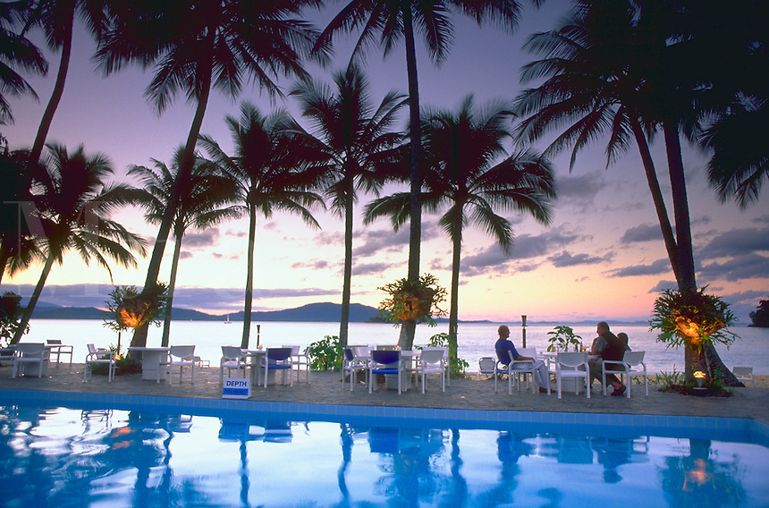 Men sitting at a table having cocktails beside a pool, surrounded by palm trees, on the coast line of Dunk Island in the Great Barrier Reef, Australia with clouds and sunset in the background.<br />
