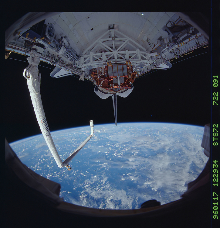 John Angerson. STS-72 Book.<br /> Public Domain Image.<br /> NASA images Courtesy National Archives - Record Group number: 255-STS-STS072<br /> Description: STS-72 shuttle orbiter Endeavour's payload bay with berthed Japanese Space Flyer Unit (SFU) and Office of Aeronautics and Space Technology-Flyer (OAST-Flyer). The remote manipulator system (RMS) arm is crooked over the payload bay. These views were taken with a 35mm lens on a 70mm Hasselblad camera to give a fisheye effect.<br /> <br /> Subject Terms: STS-72, ENDEAVOUR (ORBITER), PAYLOAD BAY, REMOTE MANIPULATOR SYSTEM, EARTH LIMB<br /> <br /> Date Taken: 1/17/1996<br /> <br /> Categories: Shuttle Configuration<br /> <br /> Interior_Exterior: Exterior<br /> <br /> Ground_Orbit: On-orbit<br /> <br /> Original: Film - 70MM CT<br /> <br /> Preservation File Format: TIFF<br /> <br /> feat: NON-EARTHOBS<br /> <br /> nlat: -18.3<br /> <br /> nlon: 68.1<br /> <br /> azi: 254<br /> <br /> alt: 163<br /> <br /> elev: 22