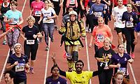 Nederland - Amsterdam - 2019 . De Marathon van Amsterdam. De finish in het Olympisch Stadion. Brandweerman rent de wedstrijd in uniform inclusief helm.   Foto Berlinda van Dam / Hollandse Hoogte