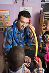 Education Preschool 3 year olds male intern or therapist working with boy in classroom, talking and listening through plastic expanding tubes