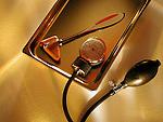 still-life of diagnostic medical tools, reflex mallet, sphygmomanometer gauge on stainless steel tray