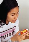 Teenage girl 15 years old reading warning labels on prescription medicine bottle