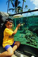 Young local boy enjoying the outdoor aqarium at the Waikiki