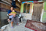 A woman with her son in front of their home in a largely Roma, Turkish-speaking neighborhood of Dobrich, in the northeast of Bulgaria.