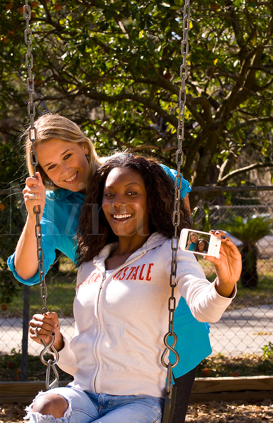 Girlfriends on a swing outdoor in sunshine, mixed ethnic, white and black African American.