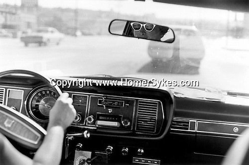 Woman wearing dark sunglasses with white frames driving through down town Los Angeles California USA 1969 .