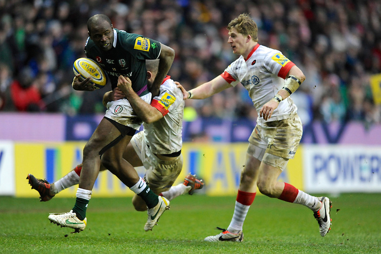 Man of the Match Topsy Ojo of London Irish is tackled by Charlie Hodgson (hidden) and David Strettle of Saracens  during the Aviva Premiership match between London Irish and Saracens at the Madejski Stadium on Saturday 9th February 2013 (Photo by Rob Munro)