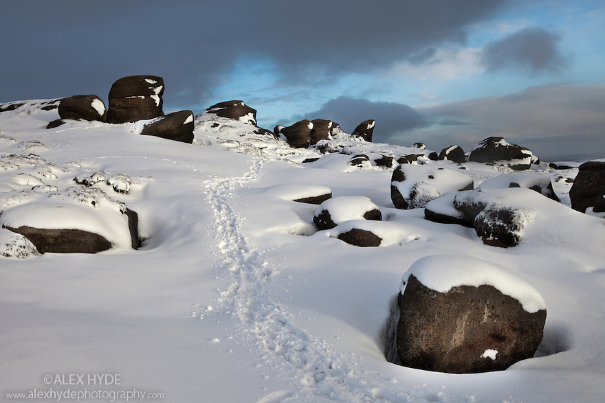 The Wool Packs, an area of weathered gritstone boulders, with path through snow winding into the distance. Peak District National Park, Derbyshire, UK. February