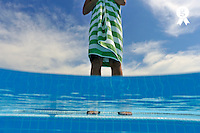 Woman standing on swimming pool ledge (Licence this image exclusively with Getty: http://www.gettyimages.com/detail/88088942 )