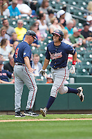 Jose Peraza (1) of the Gwinnett Braves slaps hands with third base coach Brian Snitker (4) as he rounds the bases after hitting a home run against the Charlotte Knights at BB&T BallPark on July 3, 2015 in Charlotte, North Carolina.  The Braves defeated the Knights 11-4 in game one of a day-night double header.  (Brian Westerholt/Four Seam Images)