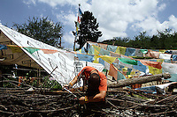 A Tibetan man adjusts prayer flags outside his home near the Jiuzhaigou National Park. Sichuan Province. China.