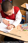 K-8 Parochial School Bronx New York Grade 1 language arts male student at work on multiple choice worksheet vertical