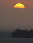 The sunsets behind Point Bonita lighthouse off the coast of San Francisco California.