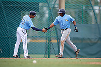 Tampa Bay Rays coach Tomas Francisco (43) congratulates Devin Davis (52) after hitting a home run during an Instructional League game against the Pittsburgh Pirates on October 3, 2017 at Pirate City in Bradenton, Florida.  (Mike Janes/Four Seam Images)