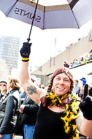 """Sean Creppel waves his Saints umbrella at the start of a parade in Buddy D's honor on January 31, 2010 in New Orleans.<br /> <br /> Thousands of Saints fans wearing dresses paraded from the Louisiana Superdome to the French Quarter to honor a promise made by the late sportscaster and Saints super-fan Buddy Diliberto aka """"Buddy D"""".<br /> <br /> In 1993 Buddy D, who passed away in 2005, remarked on air that if the Saints were to make it to the Super Bowl, he would wear a dress and dance down the streets.  The comment was repeated at various times and never forgotten by his listeners.<br /> <br /> Led by former New Orleans Saints quarterback Bobby Hebert, who has taken Buddy D's place on WWL radio, thousands made good on his promise for him, dancing, drinking, and cavorting their way down the street, alternately yelling out """"Who Dat!"""" and """"Buddy D!"""" in front of an onlooking crowd an estimated 85,000 people strong.<br /> <br /> The hard luck NFL team the New Orleans Saints has reached its first Super Bowl in team history, after 43 years largely filled with losing seasons and futility.  It is difficult to travel anywhere in the area without some reminder of this fact, as the team and city are intertwined perhaps like no other sports franchise in this country."""