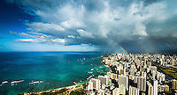 A sunrise aerial view of Waikiki (with surfers visible to the left) and downtown Honolulu, with a big rainbow touching down over Ward Avenue on O'ahu.