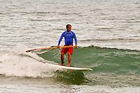 Older Hawaiian man Stand-up paddle board surfing, Kauai, Hawaii
