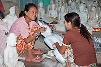 Myanmar, Burma, Mandalay.  Women Artisans at Work Polishing Buddha Carved from Stone.  Many are exported to China.