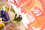 Education preschool 4 year olds still life closeup of markers, caryons, and child's colorful painting showing recognizable human being figure horizontal