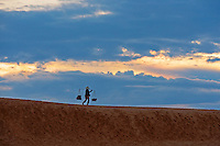 Late afternoon sunlight light and a dramatic black sky from a approaching tropical storm is setting the mood for the Mui Ne Sand dunes. <br />