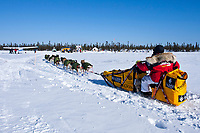 Mitch Seavey is at rest on his sled as he pulls into the Cripple checkpoint 1/2 way into the race during the 2010 Iditarod