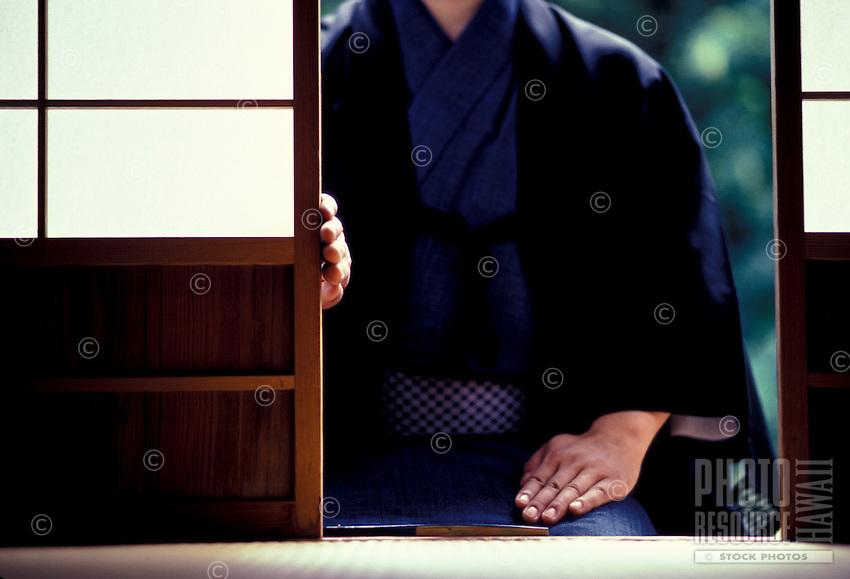 Japanese man wearing kimono sitting outside tea house