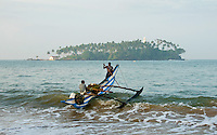 Outrigger fishing canoe crests a breaker as it is launched seaward for a day's work -Barberyn (Beruwala) lighthouse sits offshore near Bentota, Sri Lanka.
