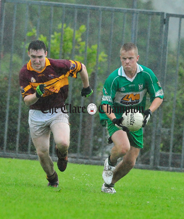Daniel Gallery of Wolfe Tones in posession as Miltown's Shane Curtin gives chase. Photograph by Declan Monaghan