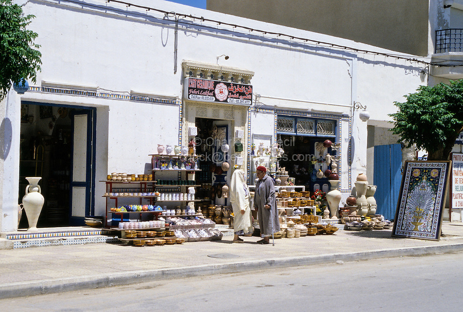 Ceramics, Nabeul, Tunisia.  Pottery Shop.  Man and Woman in Traditional Dress Talking.