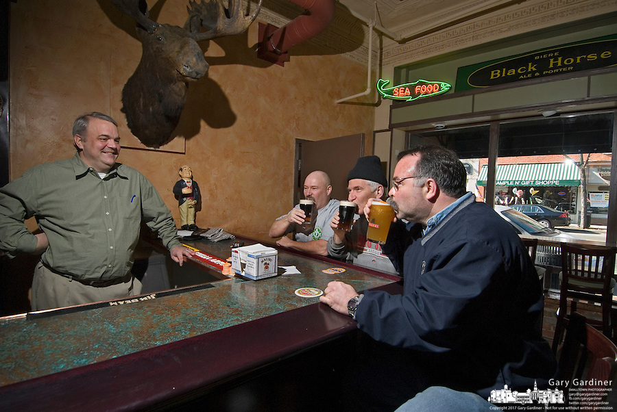 Bar owner Dave Purdum, far left, watches as opening day customers David Bruns, left, Dave Lilley, center, and Tom Ullom drink the first beers sold at Old Bag of Nails restaurant and bar in downtown Westerville, Ohio, Thursday, February 23, 2006. The business occupies a building at the main crossroads in the city that was home to the Anti-Saloon League.<br />