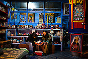 Local Bhutanese women, one dressed in jeans and the other one in traditional Bhutanese dress - kira, seen sitting in front of the heater in a handicrafts store in the capital Thimpu, Bhutan. Photo: Sanjit Das/Panos.