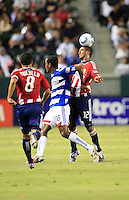 Chivas USA defender Dario Delgado (12) heads the ball away from FC Dallas forward Atiba Harris (16) during the second half of game between Chivas USA and FC Dallas at the Home Depot Center in Carson CA on June 26 2010. FC Dallas 2, Chivas USA 1.