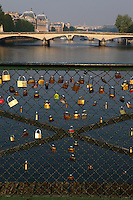 Paris: The romantic padlocks that the lovers are used to put onto the railing of the Pont des Arts (bridge of the arts) in foreground, with the view towards the center of the town in the background.