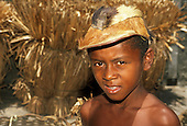 Bahia State, Brazil. Small, black boy looking into the camera wearing an animal hide hat with the fur still on it.