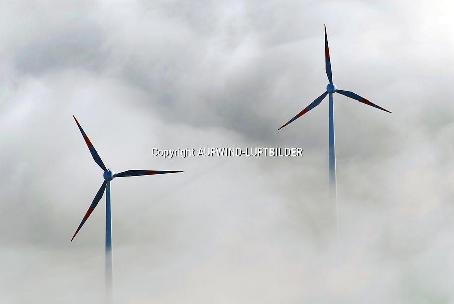 Windkraftanlagen im  Nebel: EUROPA, DEUTSCHLAND, HAMBURG, (EUROPE, GERMANY), 25.12.2005: Windkraftanlagen auf dem Shell-Raffinerie Gelaende, Hamburg Harburg. Im Herbst 2000 wurden auf dem Gelaende der Shell Raffinerie Hamburg-Harburg zwei Windkraftanlagen in Betrieb genommen. In 98 m Hoehe wird Wind in jeweils 1,8 Megawatt Leistung umgewandelt. Die erzeugte Strommenge entspricht dem Verbrauch von ca. 2.500 newpower- Kunden in Hamburg. Die beiden Enercon E-66 Windkraftanlagen mit einem Rotordurchmesser von 70 m stehen auf der Nordspitze des Raffineriegelaendes, also weit entfernt von Wohngebieten. Damit sind Geraeuschbelaestigungen und Schattenwurf fuer Anwohner ausgeschlossen. Die beiden Windkraftanlagen schauen aus dem Bodennebel heraus,